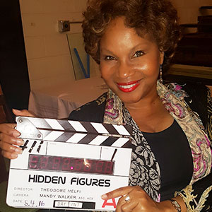 "Denise Woods is pictured, holding a clapperboard that reads ""HIDDEN FIGURES""."