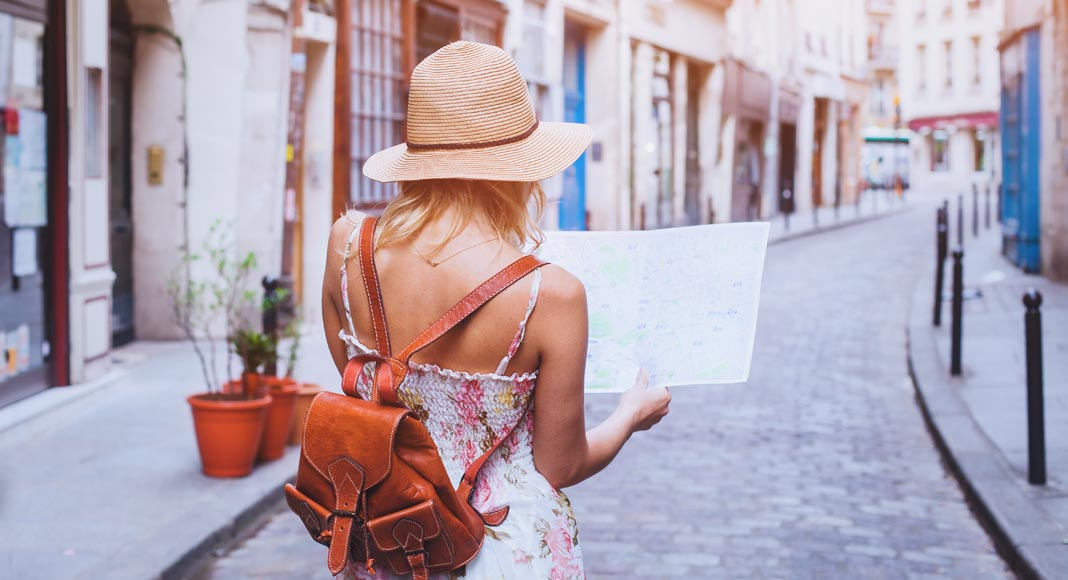 A woman in a sundress and hat holds a map in front of her face while standing on a cobblestone street.