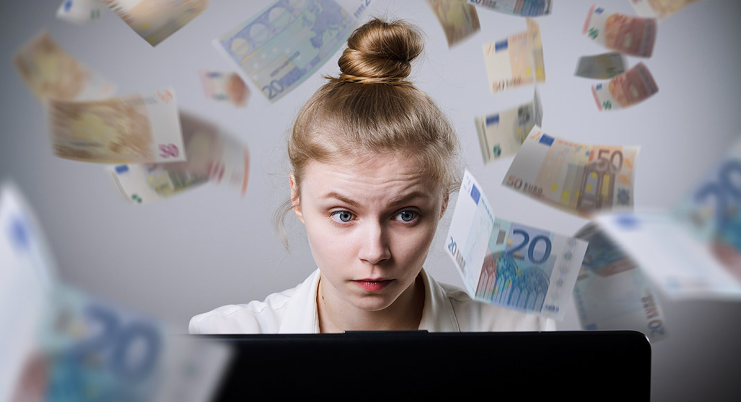 A woman looks concerned as she looks at her computer screens, while euros swirl around her