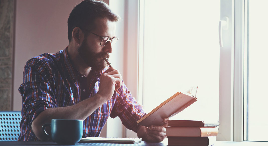A man with a beard and glasses sits at a table while looking down at a book. He has a pen pressed to his lips and a pensive expression on his face. A coffee cup sits next to him, a notebook is front of him and a small stack of books sits to the side of him.