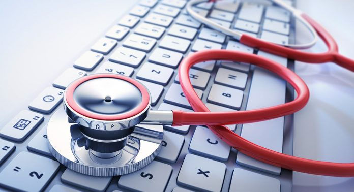 A stethoscope sits across a keyboard in a semi-unfurled fashion.