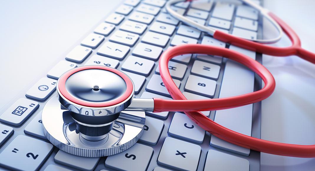 A stethoscope sits across a keyboard in a semi-unfurled fashion.