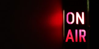 An on air sign is illuminated to the right of the image. It is lit up in red and casts a red light to the left.