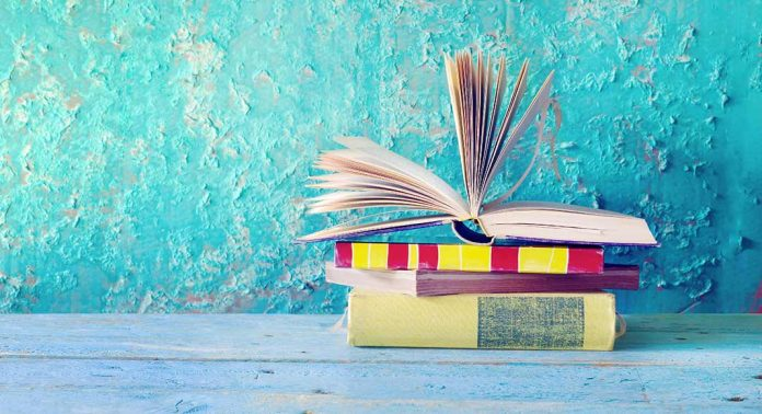 A stack of four books sits on a light blue table in front of a teal washed stucco wall