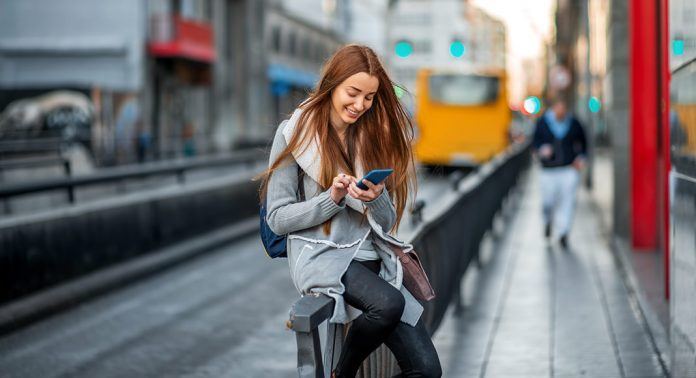 A young woman, with long, dark hair sits in a gray sweater and tights. She is smiling as she looks down at the smartphone in her hand. Behind her, blurred in the background is a train that appears to be leaving the station. There are also blurred buildings in the background. A man, also blurry, walks towards the foreground on the sidewalk to the right.
