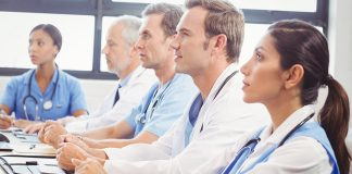 A group of medical professionals sit at a table in a row, facing right. They are wearing white coats and have stethoscopes around their necks.
