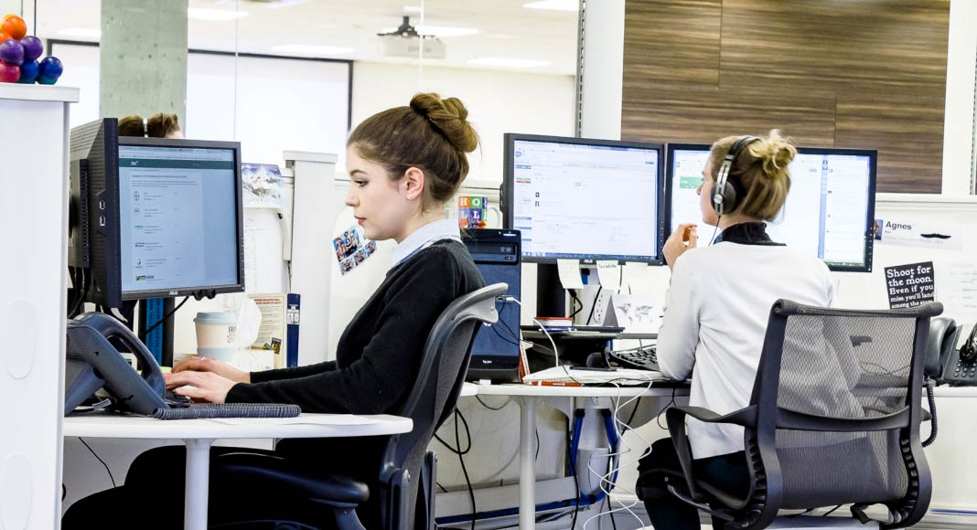 Two account managers sit at their computers in the Voices.com office.