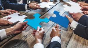 People put their hands into the centre of a table. They are holding onto puzzle pieces. One is light blue, one is dark blue.