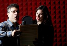 A man and a woman stand next to each other in a room with soundproofing. The man is holding a script and the woman is standing next to him, smiling. A microphone is in front of both of them.