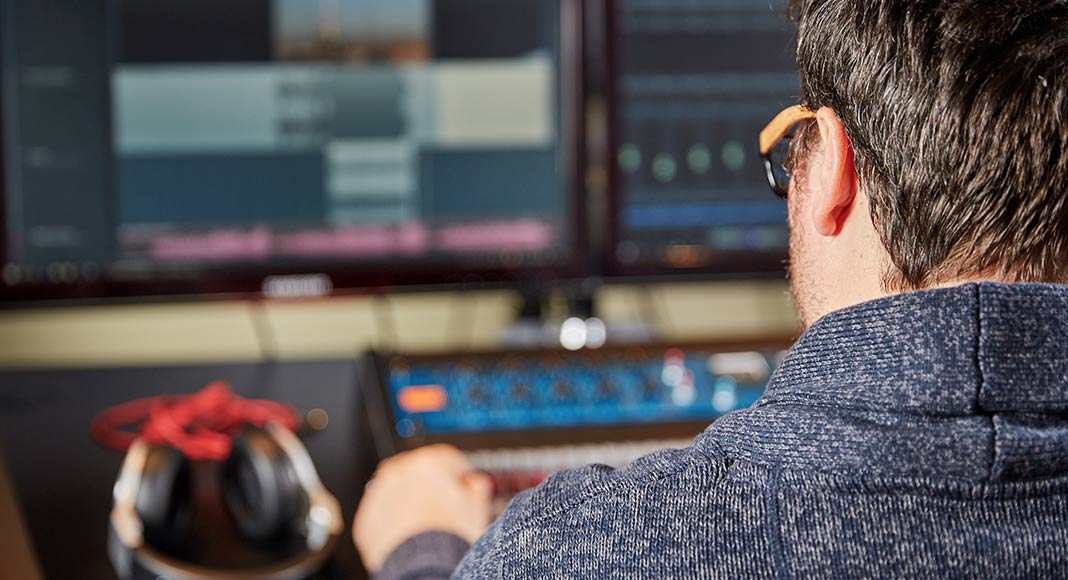 A man sits in front of a computer screen. The background is blurry, however to his left sits a set of headphones. In front of him appears to be a mixing board and vu meters. On the screen looks to be audio editing programs.