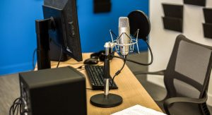 A computer and microphone on a desk, ready for recording