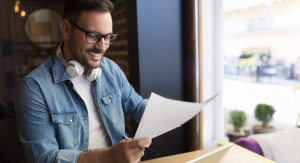 Illustration depicts man reading a script in a coffee shop