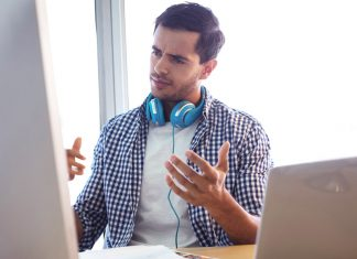 A brunette man in a plaid shirt with blue headphones around his neck stares at a computer screen with a confused expression as if he's trying to decipher a voice over script.