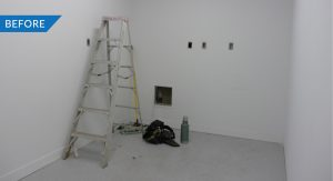 Photo of an empty white room under construction with just a ladder.