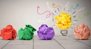 Four brightly colored crumpled pieces of paper sit on the ground while a bright yellow one is elevated and looks lit up light a lightbulb