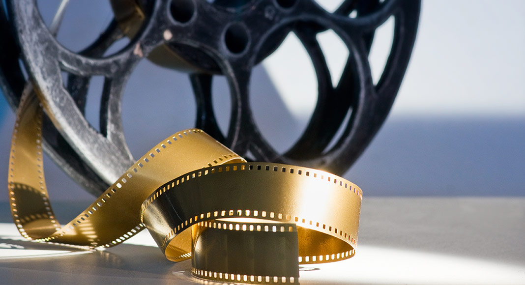 a golden film reel and unraveling film