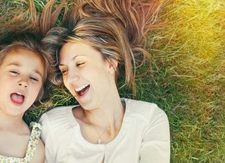 A mother and daughter lie in the grass with their mouths open, smiling and singing