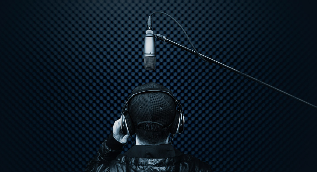 A man wearing a ballcap and headphones has his back turned to the camera as he speaks into a microphone in an isobooth