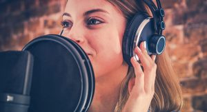 A young woman with headphones on gets close to a pop filter and microphone to speak