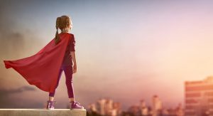 Little girl with a cape on stands at the top of a building with the wind in her hair