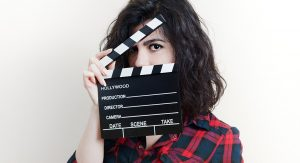 A woman holds a clapper half open as she looks at the camera