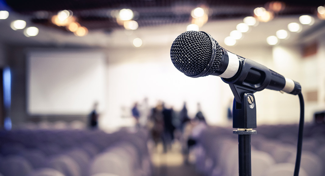 A microphone sits in focus while the background of empty chairs in a conference venue is hazy