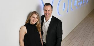 Stephanie and David Ciccarelli pose in front of the Voices.com sign in their 45,000 square foot office in London, Ontario, Canada