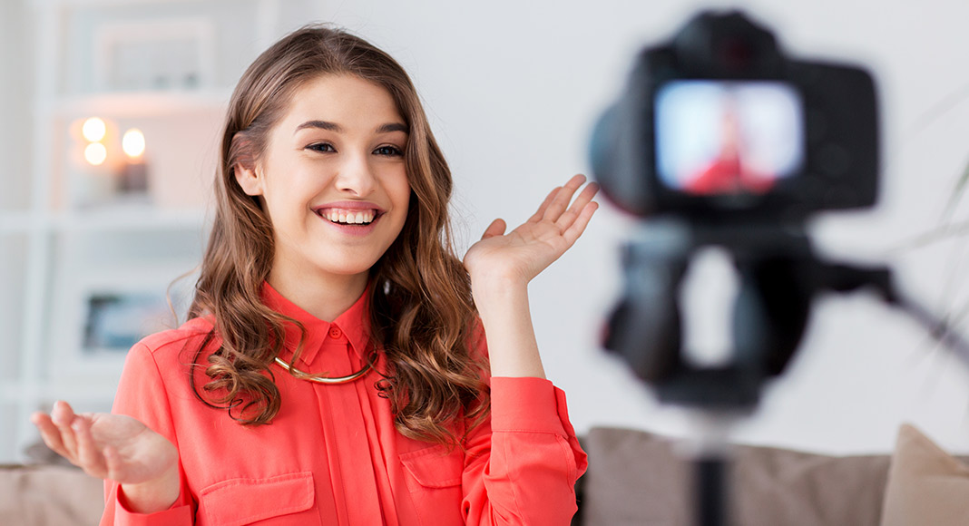 A young woman smiles as she records herself for a YouTube video.