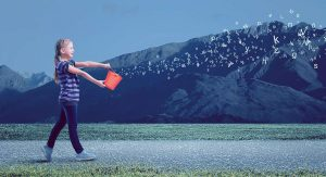 A young girl tips a bucket and out of it flows a flurry of letters, out into the wind
