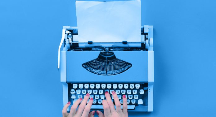 A woman types on a blue typewriter