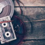 A reel of tape and a cassette sit on a wooden floor