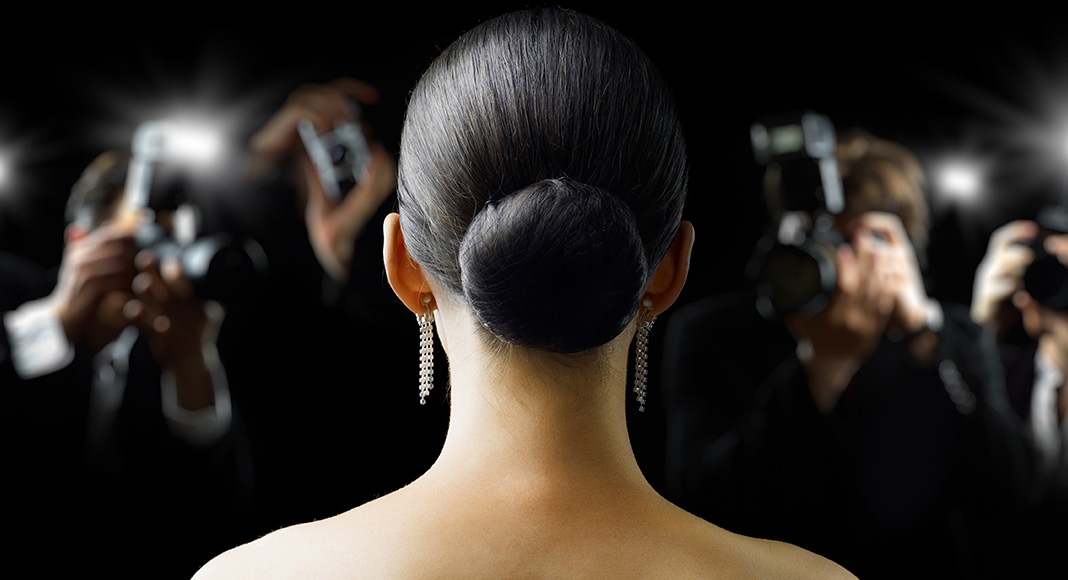 View of a woman's face from behind, before her, we see that there are paparazzi taking photos. She looks like she's on a red carpet and is dressed elegantly.