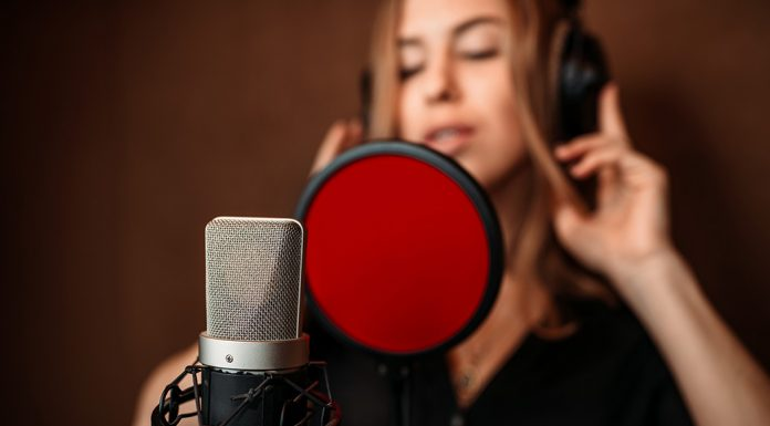 A female singer stands in the background. In the foreground is a microphone with a red pop filter in front of it.