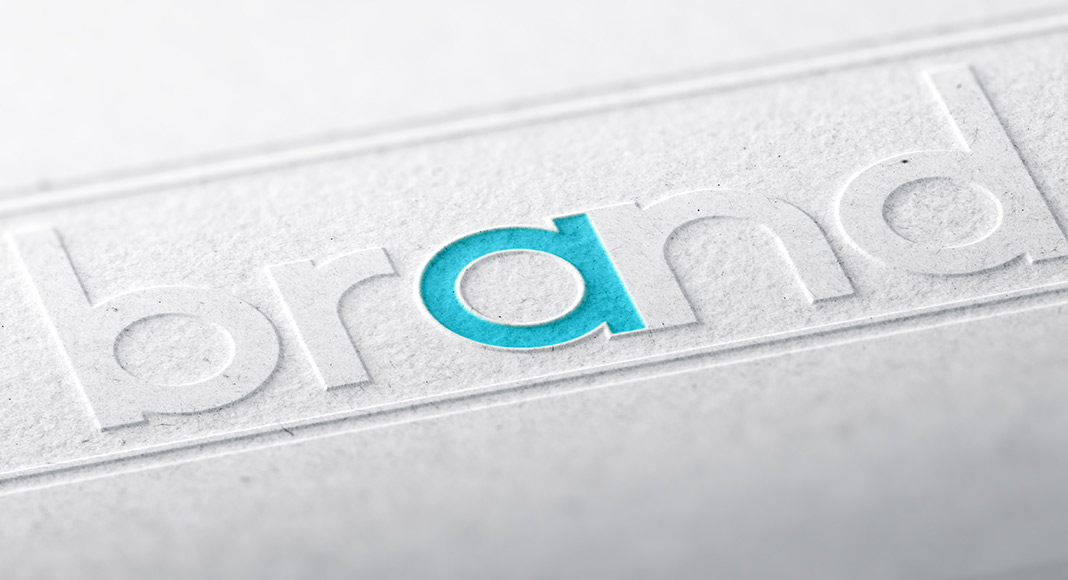 "The word brand is embossed in lower case letters, diagonally across a piece of paper. The ""a"" is teal, while everything else is grey."