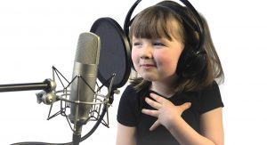 A child voice actor, a little girl around 4 years old sits in front of a microphone with headphones on