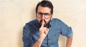 Man with finger over mouth to signal be quiet