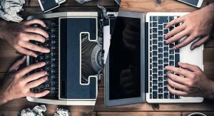 A typewriter is pushed up against a laptop