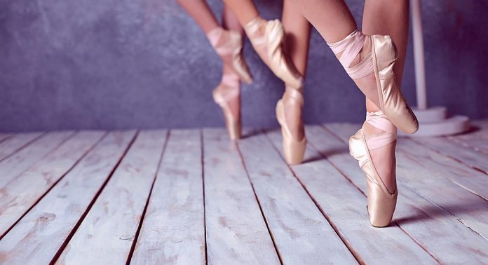 close up on the feet of three ballet dancers standing eleve
