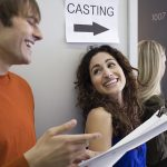 a man and a woman laughing infront of casting audition sign | Voices.com Blog - Where clients and voice actors can find valuable information on pre-production, technology, animation, video and audio production, home recording studios, business growth, voice acting and auditions, celebrity voice actors, voiceover industry news and more!