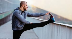 man stretching his leg on a railing before running | Voices.com Blog - Where clients and voice actors can find valuable information on pre-production, technology, animation, video and audio production, home recording studios, business growth, voice acting and auditions, celebrity voice actors, voiceover industry news and more!