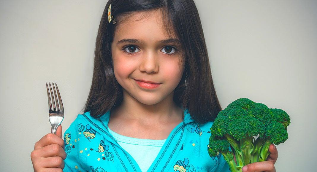 Tweenaged girl not wanting to eat broccoli.