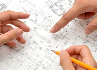 Three hands are pointing to a technical paper with a pencil drawing.