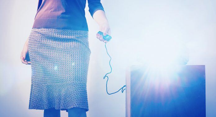 a woman holds the remote for a projector, while light flashes.