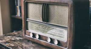 An old-school am radio sitting on a wooden table in someone's book room.