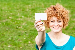 Red haired woman smiling holding up a piece of paper | Voices.com Blog - Where clients and voice actors can find valuable information on pre-production, technology, animation, video and audio production, home recording studios, business growth, voice acting and auditions, celebrity voice actors, voiceover industry news and more!