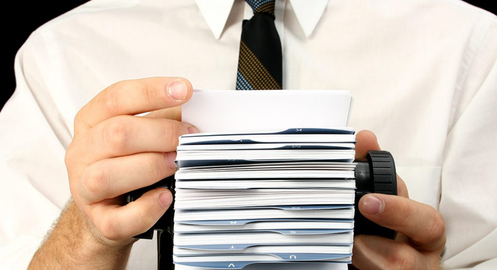 A man in a suit flips through a Rolodex