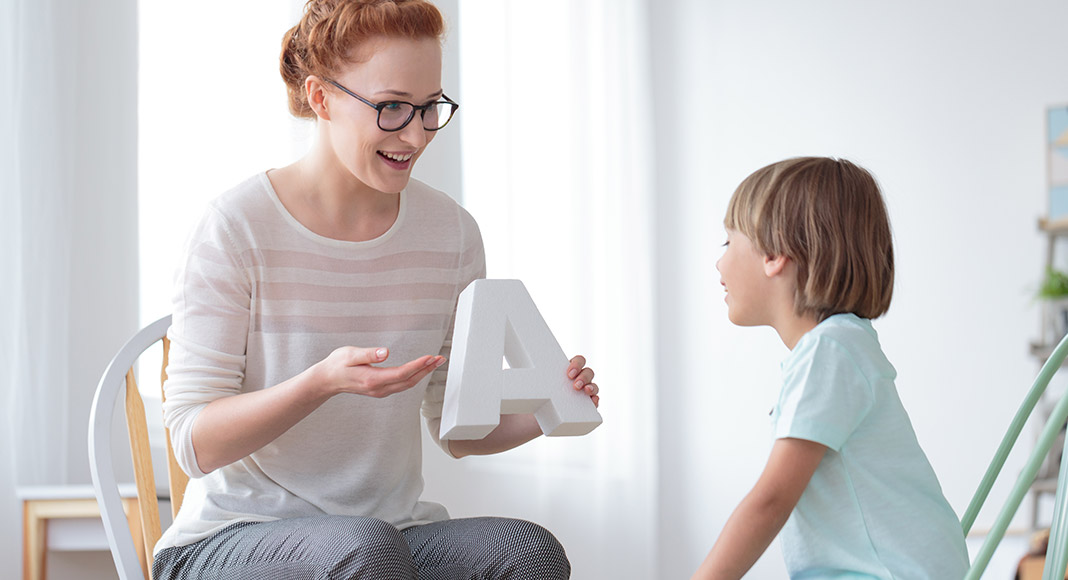 A woman explaining the letter A to a child