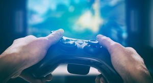 viewpoint shows two hands on a videogame controller in the foreground, while a brightly lit television screen is visible in the background.