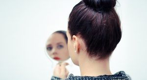 Woman holding a hand mirror and looking at her reflection.