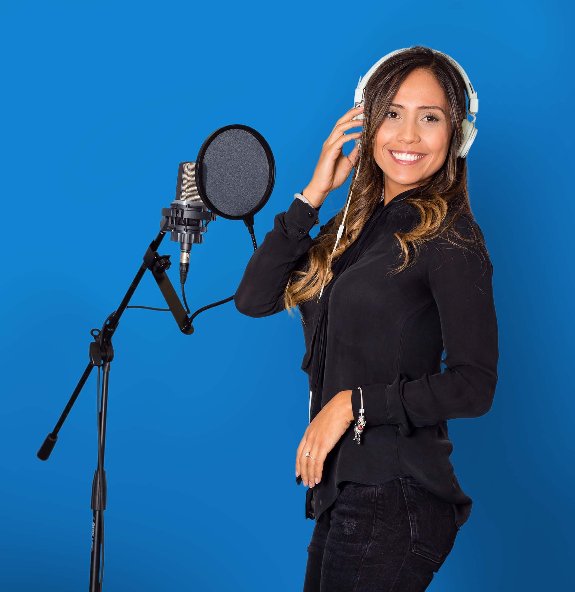 A woman standing in front of a microphone against a blue background, while putting a hand to her headphones.